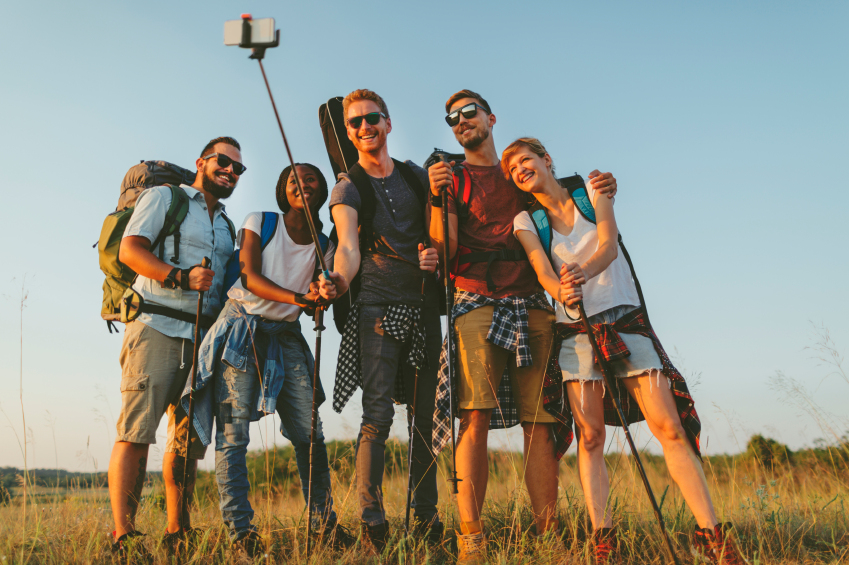 Group of young hikers making group selfie with smart phone and selfie stick. They enjoy sunny day and having fun. Male in the middle holding selfie stick. All of then looking at camera and smiling, and holding hiking poles in hands. Males are wearing sunglasses.