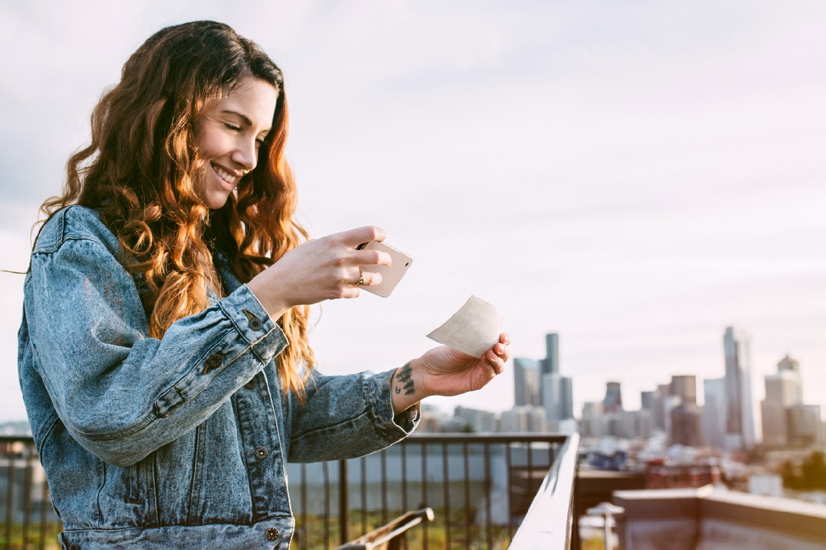 A beautiful Caucasian adult woman on a Seattle roof top taking a picture of a check with her smart phone for a Remote Deposit Capture.  She smiles, wearing modern stylish clothing.  Seattle cityscape on the skyline in background.